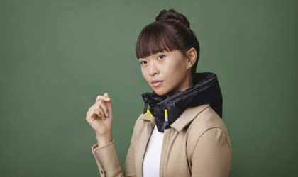 A woman is against a jade-green background is wearing a black airbag collar around her neck.