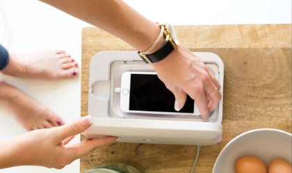 A top down view of a woman placing a smartphone into a white cleaning case.