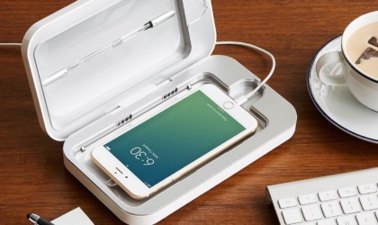 A smartphone is sitting inside a cleaning device, and it is also plugged in to charge.