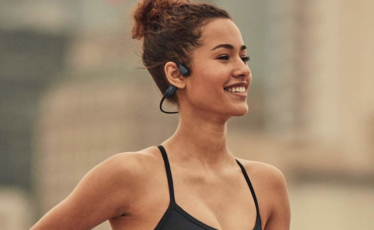 A woman is smiling and wearing a pair of headphones.