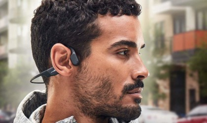 A side view of a man wearing a pair of black headphones.