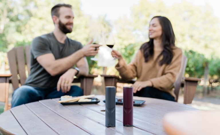 A man and a woman are holding glasses of wine, and there are two wine decanter gadgets on the table in front of them.