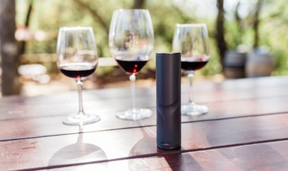 Three glasses of red wine are on a table behind a wine decanting device.
