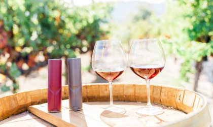 Two glasses of wine are sitting next to two wine decanting devices