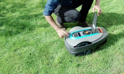 A man is opening the lid to the display of a robot lawnmower.