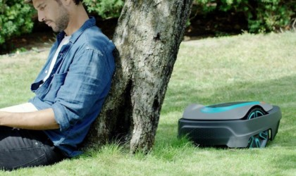 A man is sitting against a tree, and there is a robot lawnmower behind him.