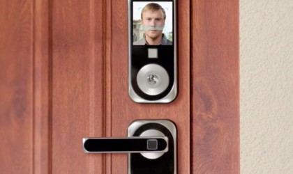 A facial recognition screen with a man's face is mounted above a door handle.
