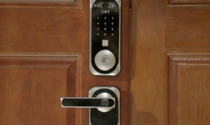 A door handle has a key pad entry device mounted above it.