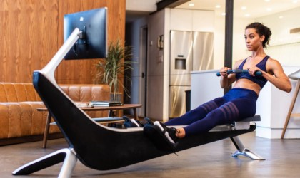 A woman is using a compact rowing machine in what looks like an office space.