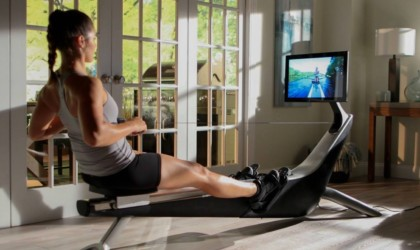 A woman is using a rowing machine and watching a class on the screen.