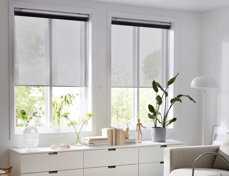A pair of light blinds are halfway lowered in a white bedroom.