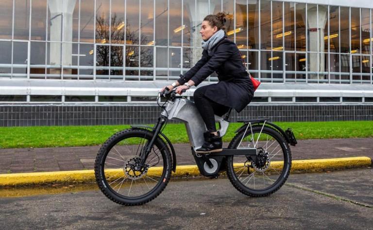 A woman is riding an all-terrain ebike down the street.