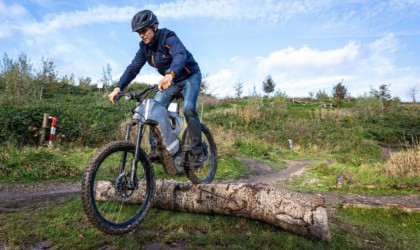 A man is riding an eBike over a log.