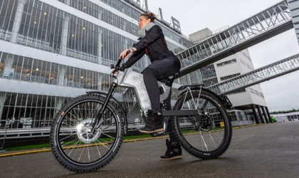 A woman is riding an eBike through the city.