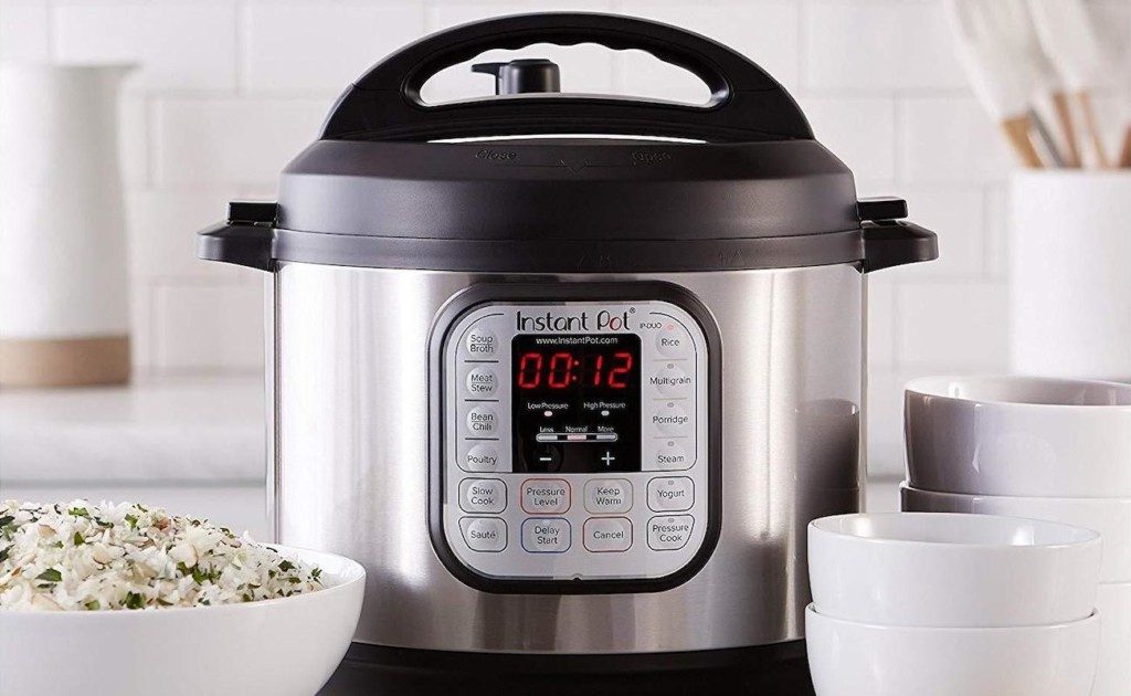 A black and silver Instant Pot is on a counter with white bowls on either side of it.