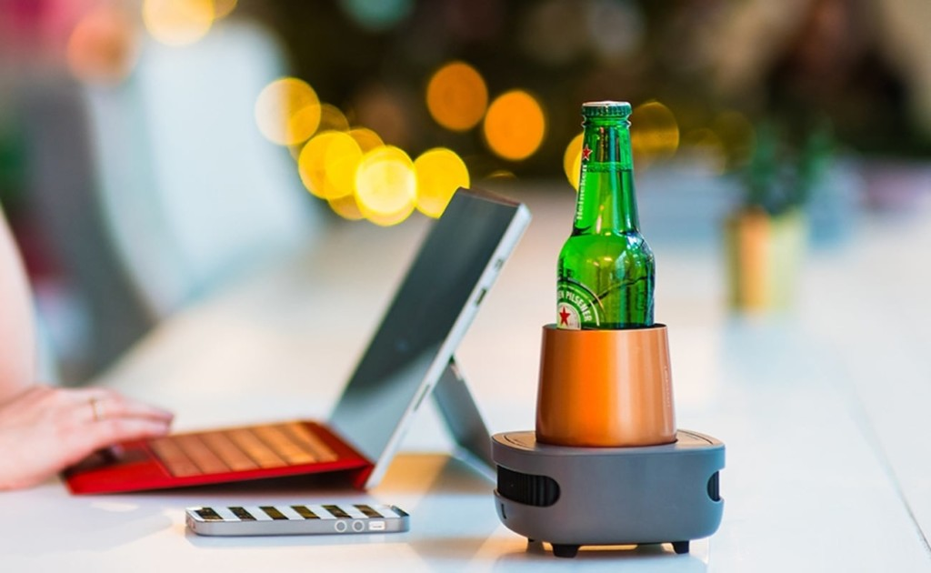 A bottle of beer is in a cooling device on a table, next to a laptop.