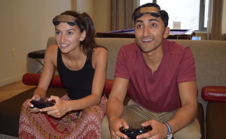 A woman and a man are playing video games and wearing neurostimulation headbands.
