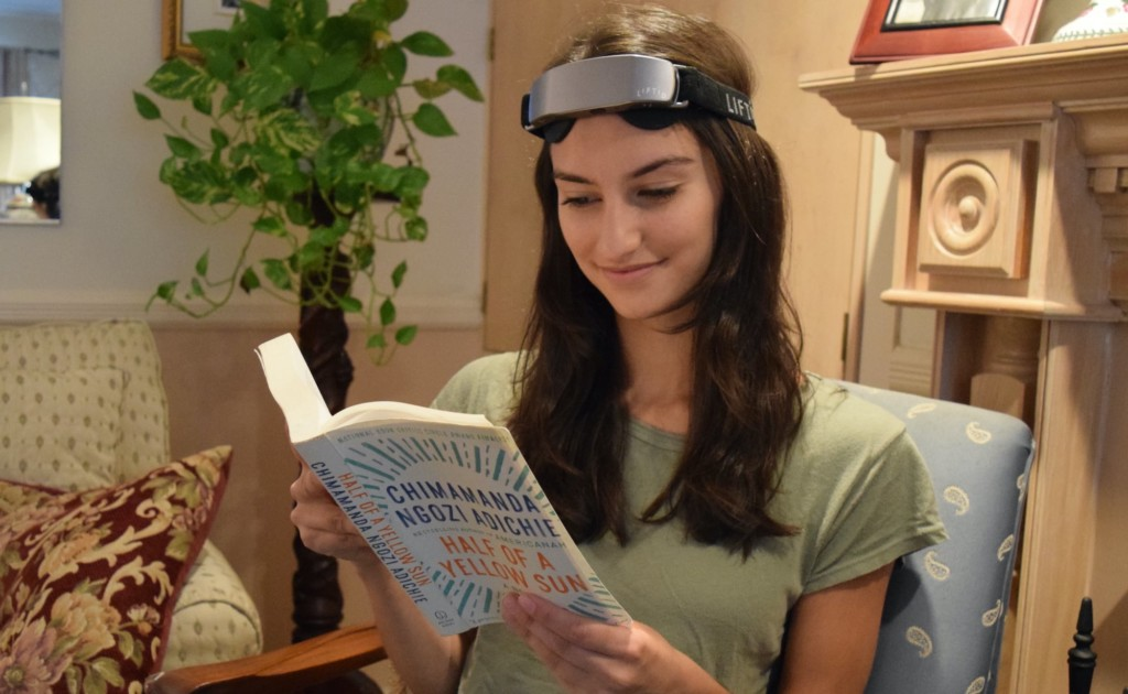 A woman is sitting in a chair, reading and book and wearing a neurostimulation headband.