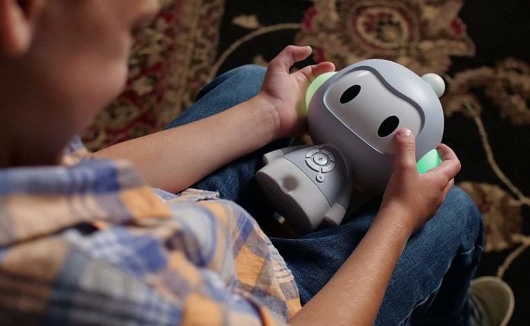 A child is sitting on the ground and holding a cute storytelling robot in their lap.