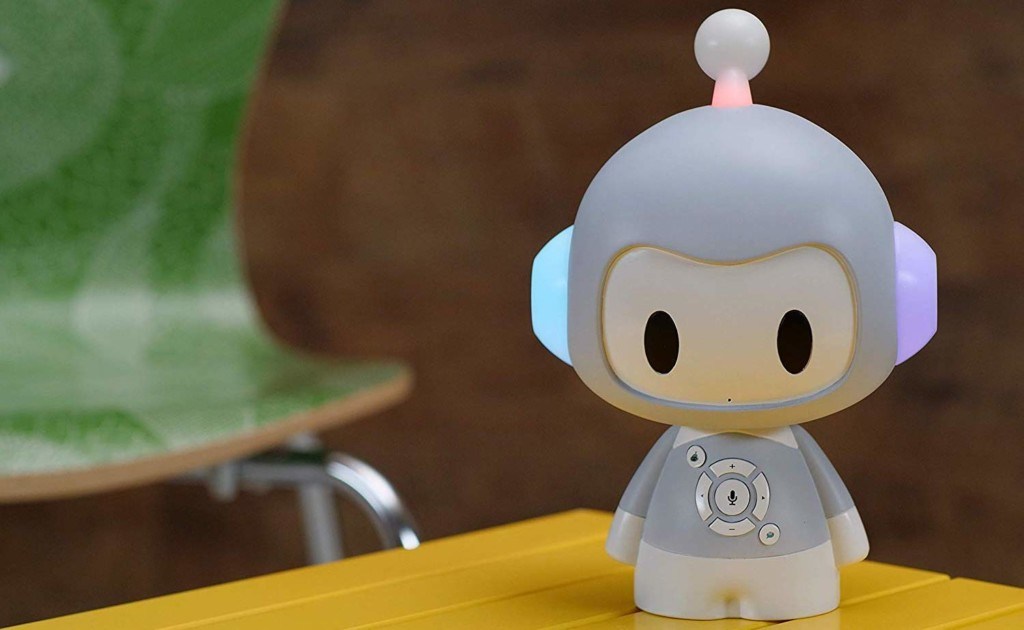 A cute storytelling robot is sitting on a wooden table.