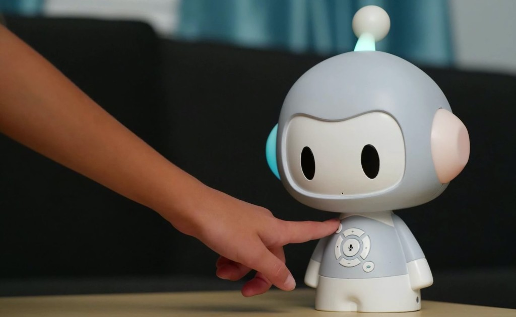 A child is reaching out to press a button on a storytelling robot.