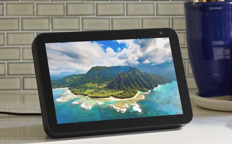 A tablet is sitting on a white kitchen counter, and it has a picture of an island on the screen.