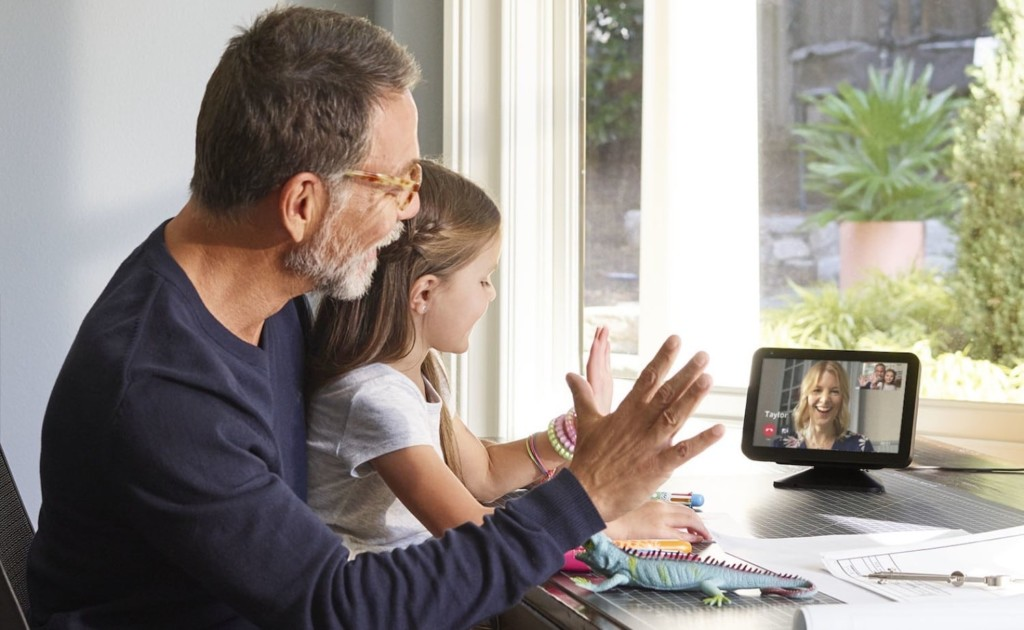 A man and a little girl are looking at a tablet and waving to a woman on the tablet screen.
