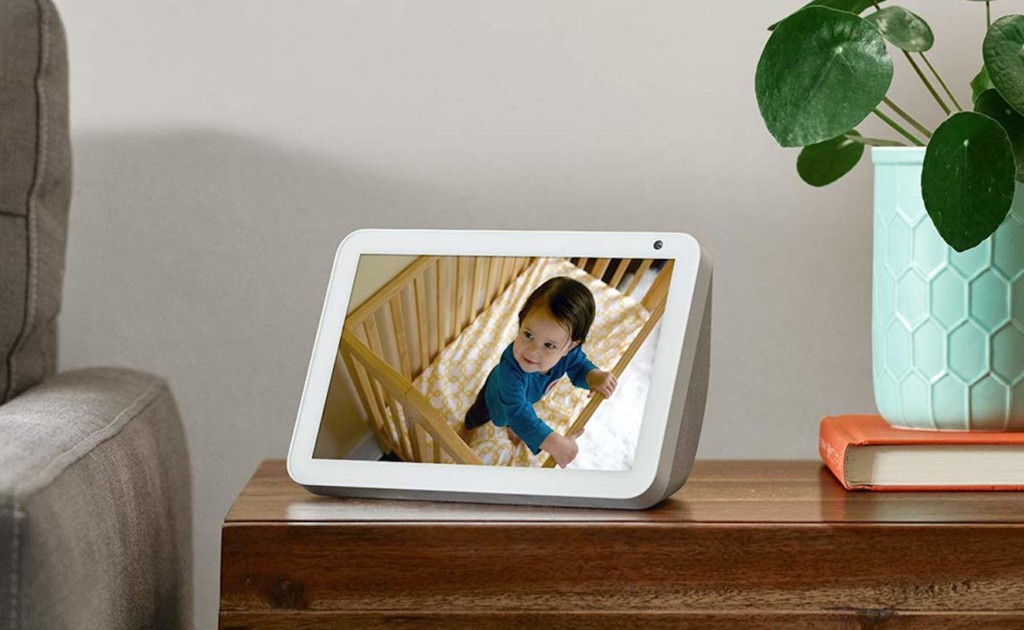 A white tablet is sitting on an end table, and there is a baby in a crib showing on the screen.