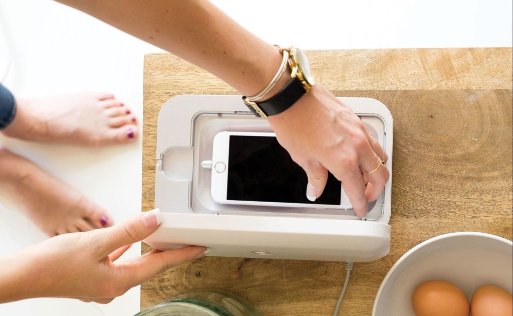 A woman is positioning a smartphone in a smartphone cleaning device.