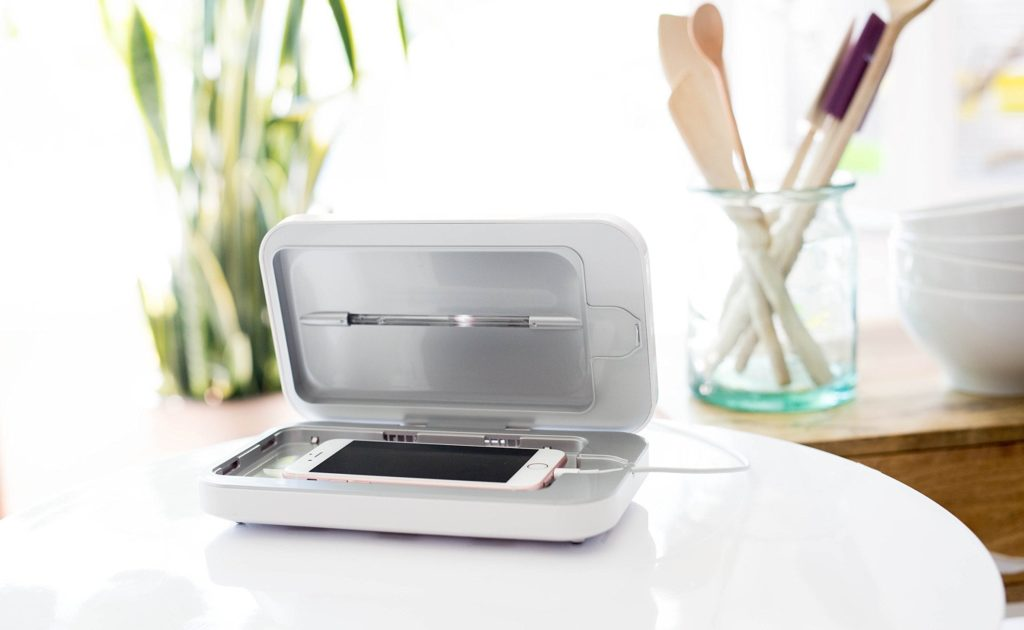 A smartphone cleaning device is open on a table, and there is a smartphone charging inside of it.