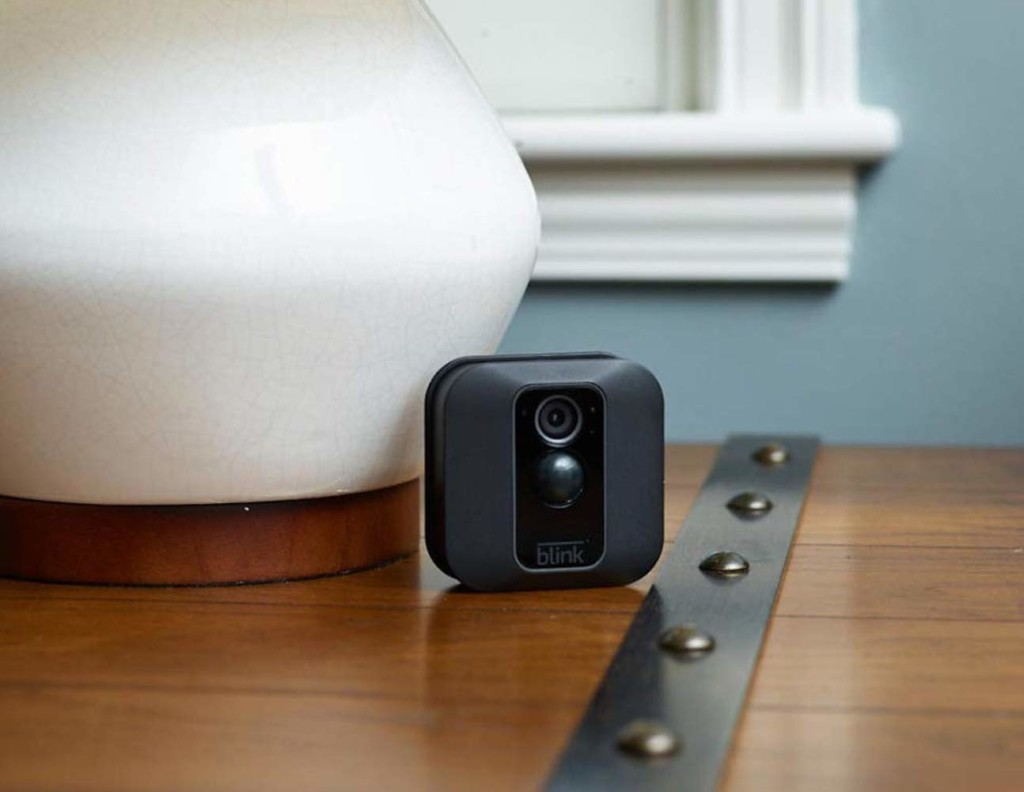 A small, square black camera is sitting on a wood table next to a white lamp.