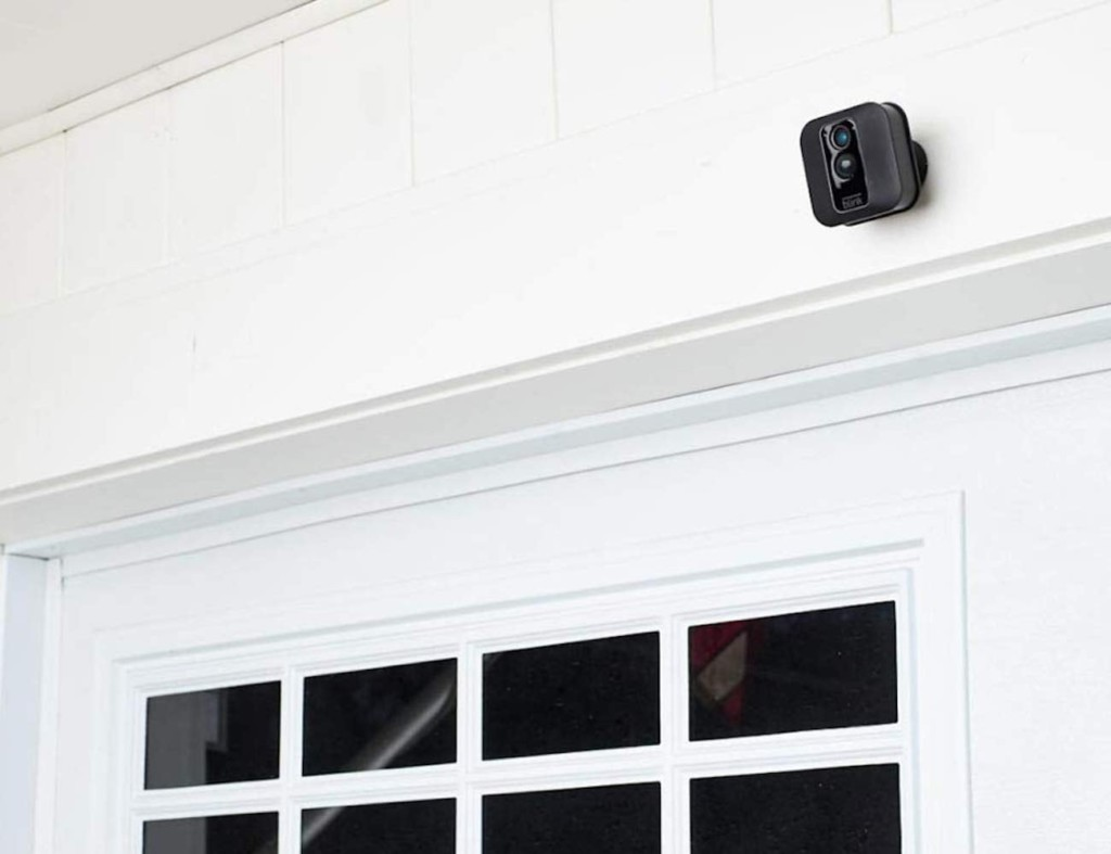 A small black camera is mounted about a white garage door.
