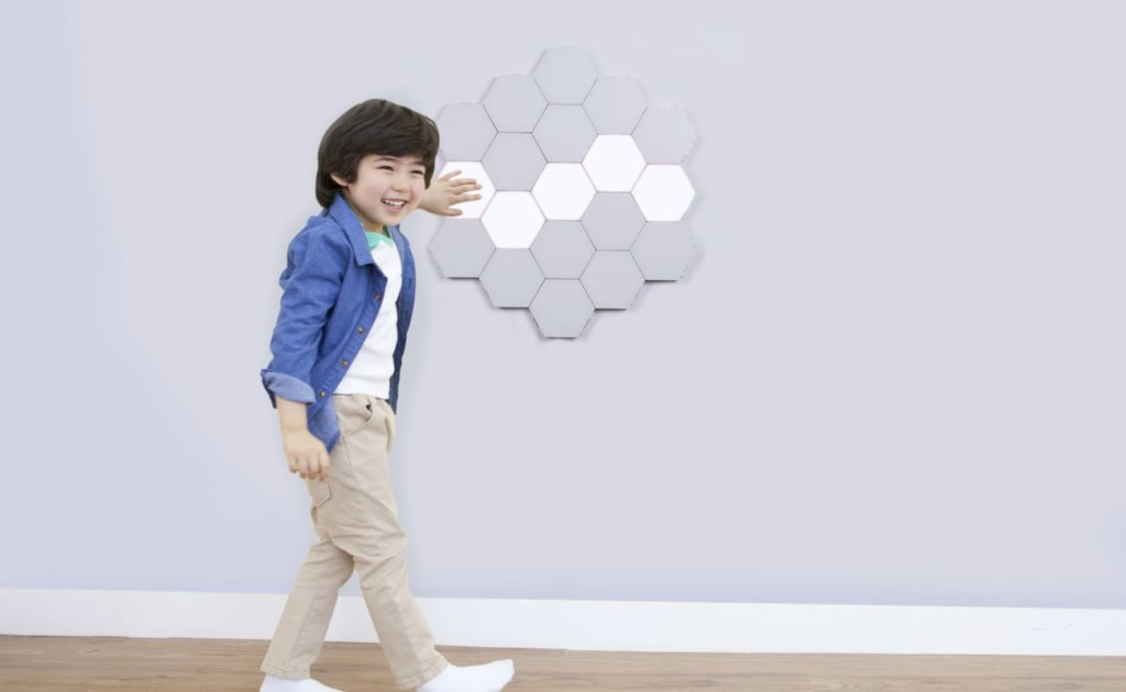 A child is walking by a group of touch lights on a wall and reaching out to touch them.