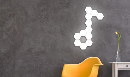 Lights in the shape of a music note are on a dark gray wall with a yellow chair below.