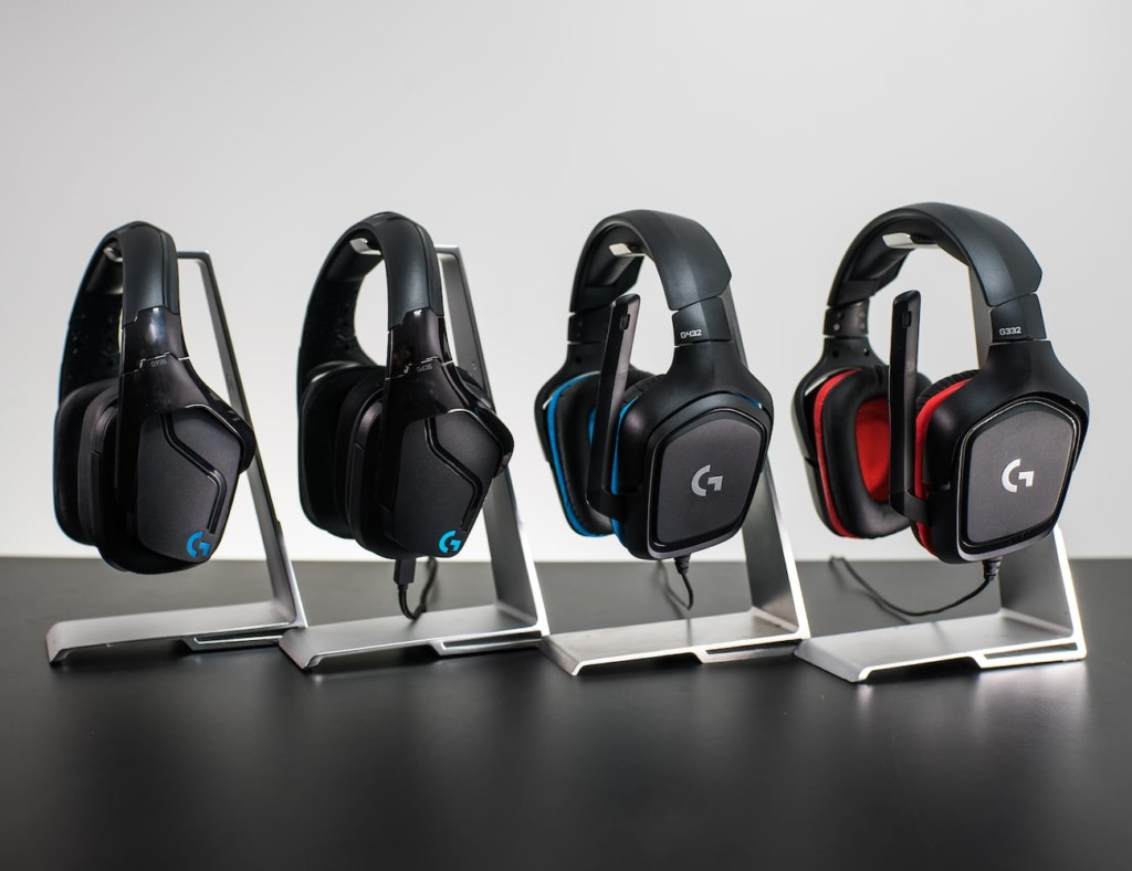 A row of four black headphones hanging from headphones stands in a row.