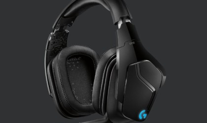 A pair of black headphones against a dark background.