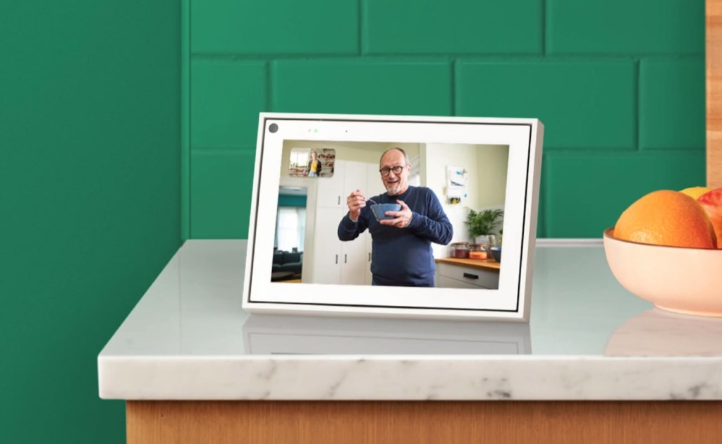 A white tablet is sitting on a marble countertop with a green brick background.