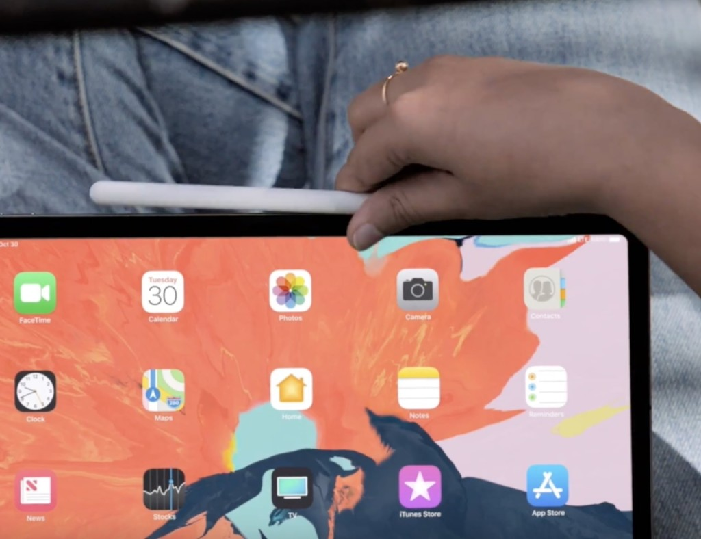A person is holding an iPad Pro and attaching an Apple Pencil to the side.