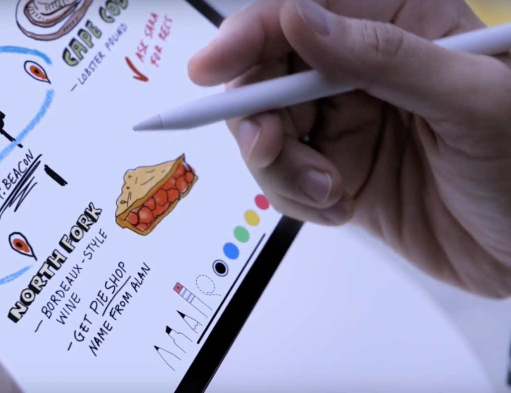 A person is holding an Apple Pencil and drawing on an iPad Pro.