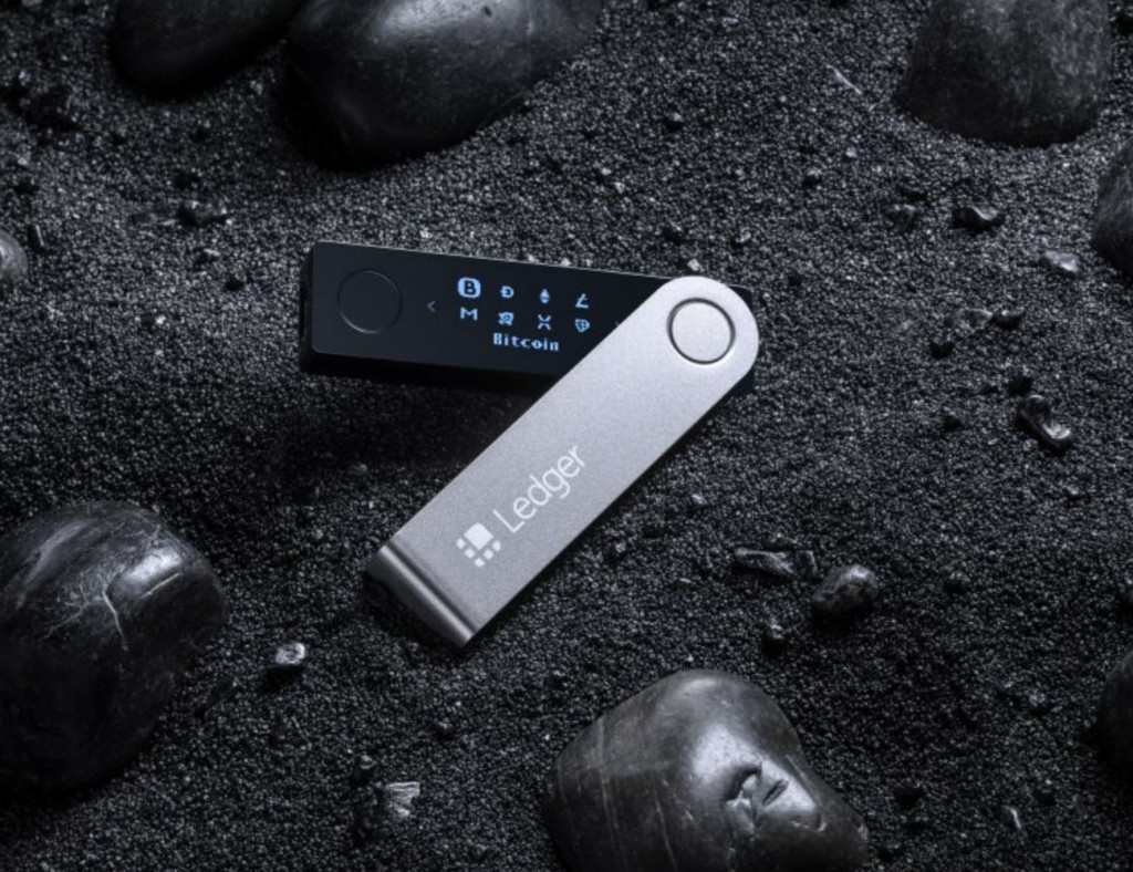 A small black cryptocurrency device is on a black background.