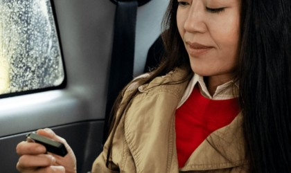A woman is sitting in a car holding a smartphone and a small black cryptocurrency device.