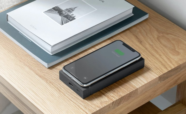 A wireless powerbank is sitting on a table next to a pile of books, and there is a smartphone on the power bank.