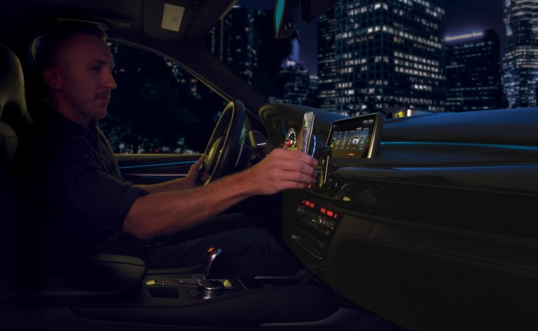 A man is driving a car and placing his smartphone on a wireless car charger.
