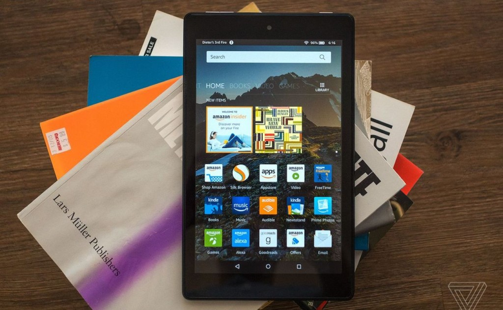 A tablet open to the home page with the app icons is sitting on top of a pile of books.
