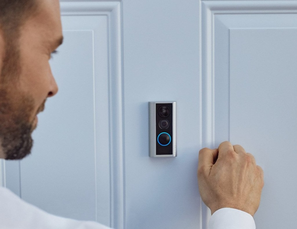 A man is knocking on a white front door, and there is a peephole camera on the door.