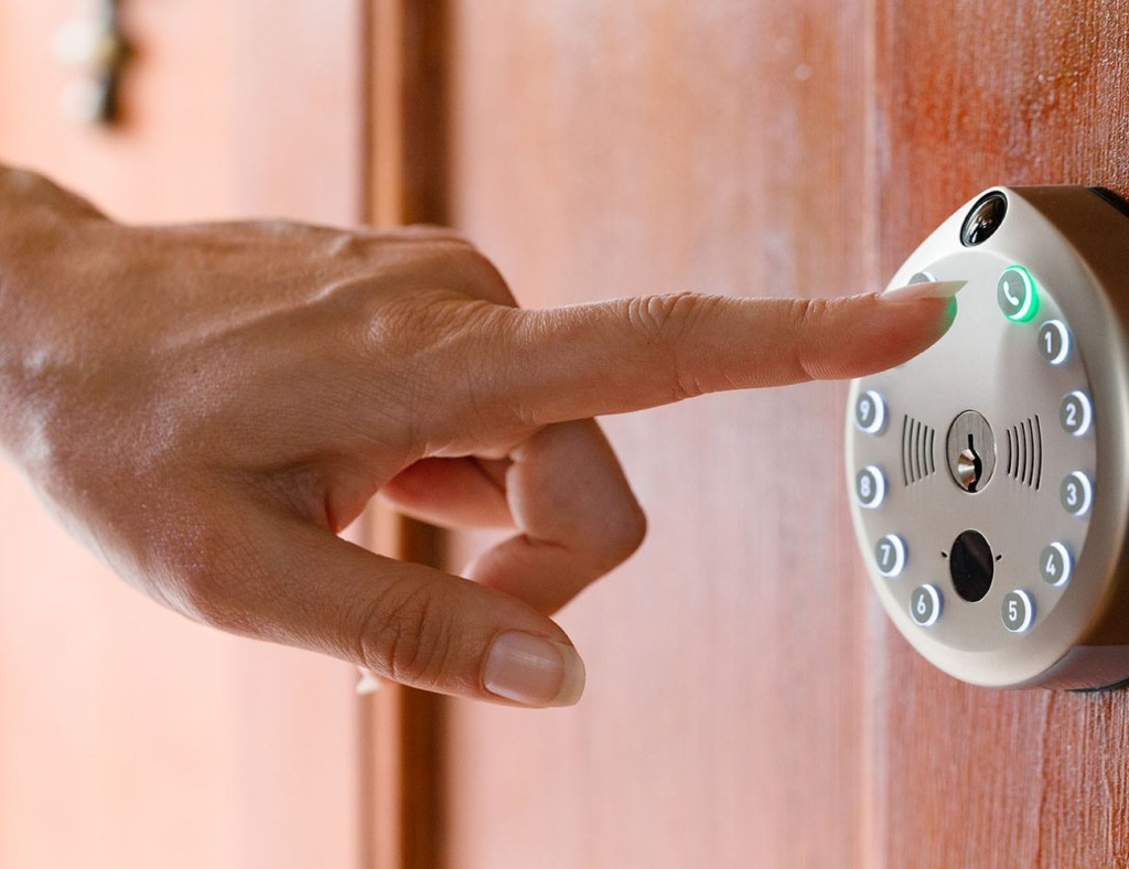 A woman's hand is reaching out to press the button on an automatic lock on a door.