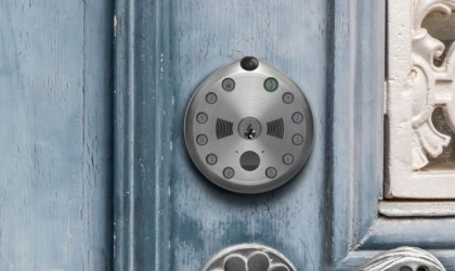 A round keyless door lock is on a blue door.