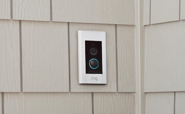 A rectangular black and white doorbell camera on beige siding.