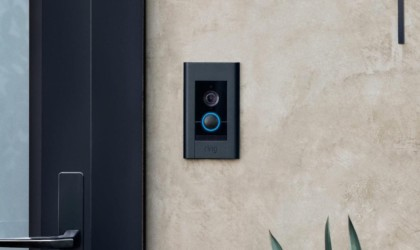 A black rectangular doorbell video monitor is on a tan house.