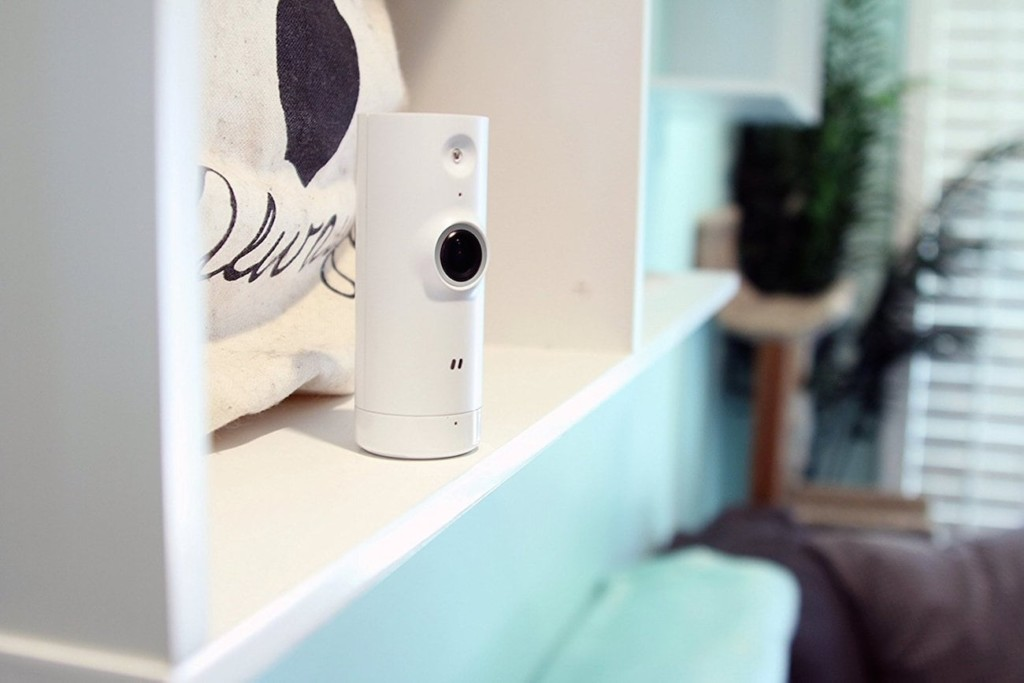 A small, white cylinder camera is on a bookshelf.